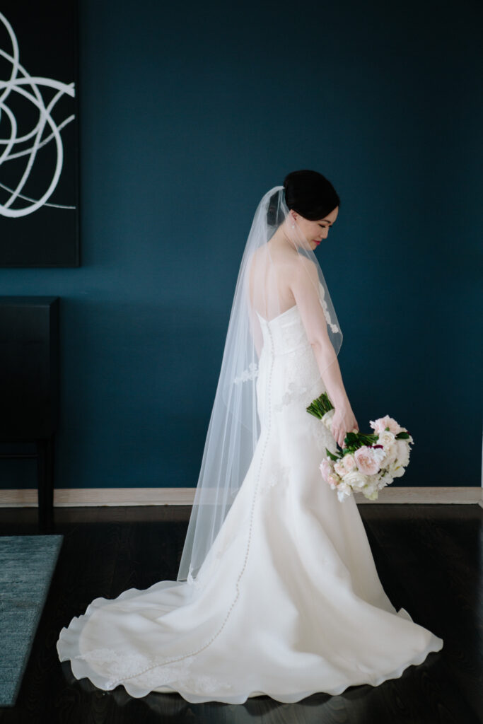 Bride in satin gown and lace trimmed vail