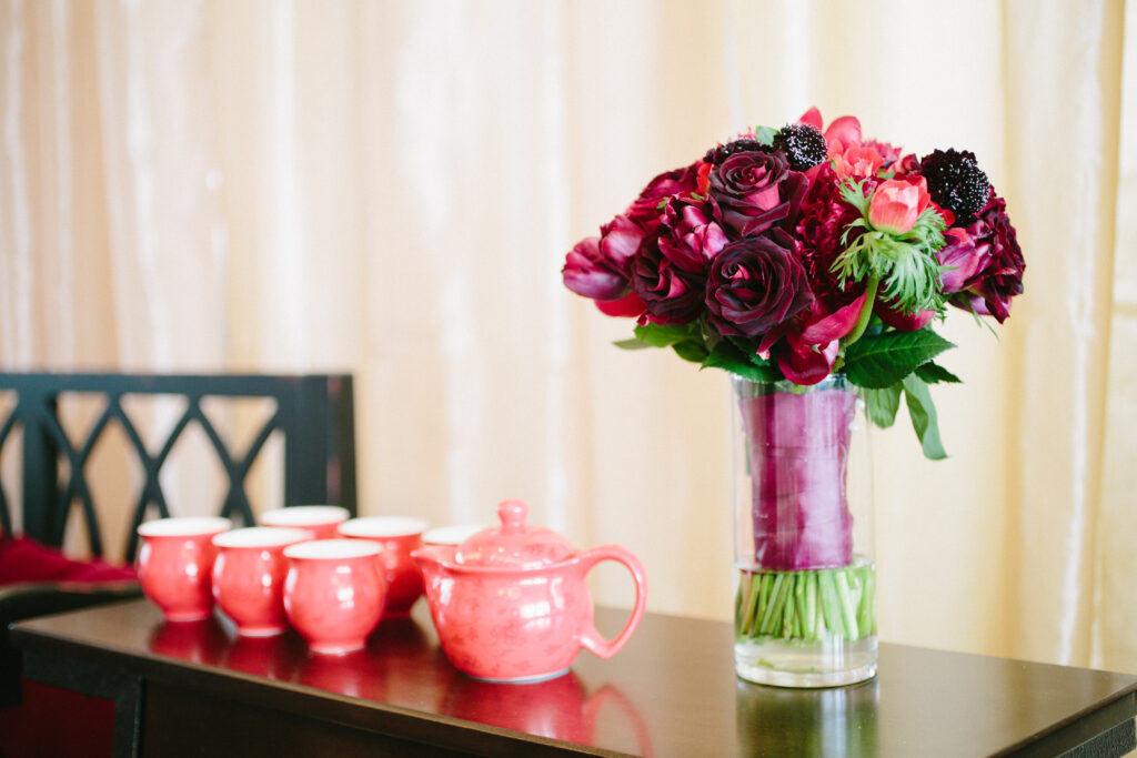 Traditional tea ceremony with red florals and tea cups.